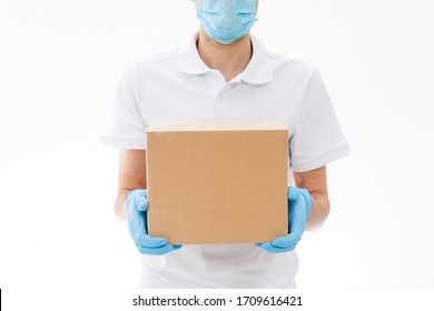 home delivery, online order. A man in uniform, a medical mask and rubber gloves with a box, a parcel in his hands. Food and food delivery during the quarantine of the coronavirus pandemic