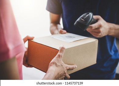 Home delivery service and working service mind, Woman customer hand receiving a cardboard boxes parcel from service courier and deliveryman scan barcode to confirm delivery.