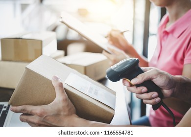 Home delivery service and working service mind, deliveryman working barcode scan checking order to confirm sending customer in post office.