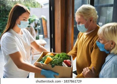 Heimlieferservice für junge Frau, die frisches Essen in Pappschachtel an erwachsene Paare übergibt. Spende oder Online-Lieferung von Nahrungsmitteln. Virus- und Quarantänekonzept