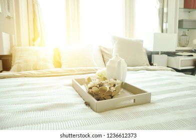 Home Design Concept. Serve tea in the morning at bedroom in the morning. Bedroom interior design  with luxury white pillows on bed and decorative table lamp.
