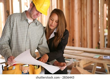 A home designer working with a home builder and inspecting the blueprints