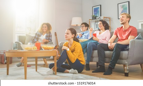 At Home Diverse Group Friends Watching TV Together, Eating Snacks and Drinking Beverage. They Probably Watching Sports Game, Movie or Sitcom TV Show. Young People Having Fun Together.