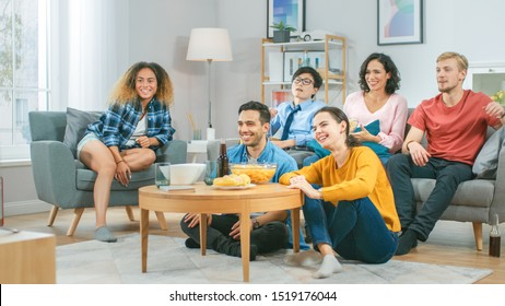 At Home Diverse Group Friends Watching TV Together, Eating Snacks and Drinking Beverage. They Probably Watching Sports Game or Movie. Young People Having Fun Together.