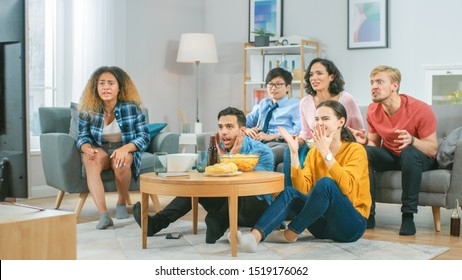 At Home Diverse Group Friends Watching TV Together, Eating Snacks and Drinking Beverage. They Probably Watching Sports Game or Fun Movie.