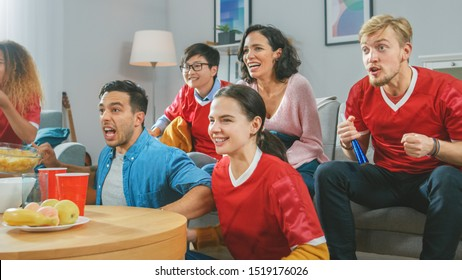 At Home Diverse Group of Sports Fans Wearing Team's Uniform Watch Sports Game Match on TV, They Cheer for the Team, Celebrate Victory after Team Scores a Winning Goal. Cozy Room with Snacks and Drinks