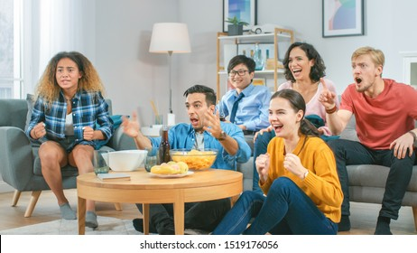 At Home Diverse Group of Sports Fans Sitting on a Couch Watching Important Sports Game Match on TV, They Cheer for the Team at a Very Tense Moment. Cozy Room with Snacks and Drinks.