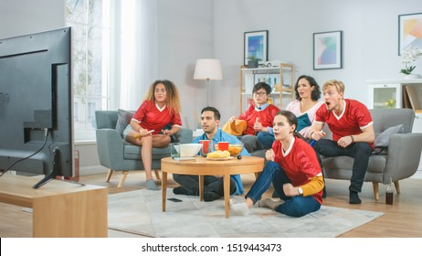 At Home Diverse Group of Sports Fans Wearing Team's Uniform Watch Sports Game Match on TV, They Cheer for the Team. Cozy Room with Snacks and Drinks
