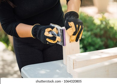 Home DIY project. Sanding down a 2 by 4 piece of wood with sand paper by hand on a sunny day. Summer DIY home project, preparing to paint and stain the 2x4 lumber of wood. DIY carpenter work.