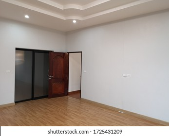 Home door interior in empty room  .Open brown door in the modern house with slide door, white wall and brown laminate floor.