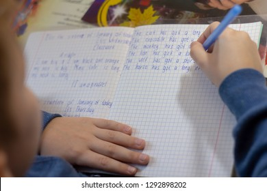 Home education and work after school. Boy hand with pen writing english test by hand on traditional white notepad paper