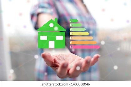 Home energy efficiency concept above the hand of a woman in background