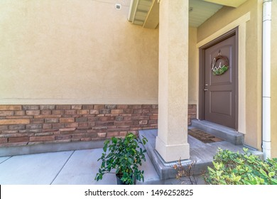 Home entrance with doorstep small porch and brown wooden front door with wreath