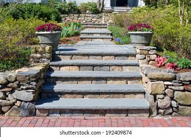 Home entrance walkway, stone wall, bluestone steps and big planters