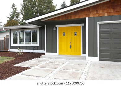 Home entrance with yellow front doors of a lovely gray house.