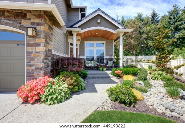 Home exterior with garage and driveway, patio area with nice landscaping desing around