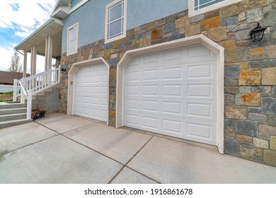 Home exterior with two car attached garage and stairs going up to the entrance