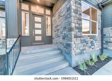 Home facade with stone brick wall and gray front door with frosted glass panels. Sidelights, front window, stairs, and railing can also be seen at the house exterior.