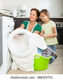 Home family laundry. Happy mother with playful daughter loading clothes into washing machine in kitchen