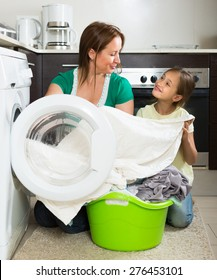 Home family laundry. Smiling mother with little daughter loading clothes into washing machine in kitchen. Focus on woman