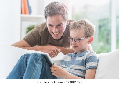 At home, a father and his young son having fun by gaming on a tablet, kid sits on a white couch and dad looks at the screen over the shoulder of his son and giving him advices to win