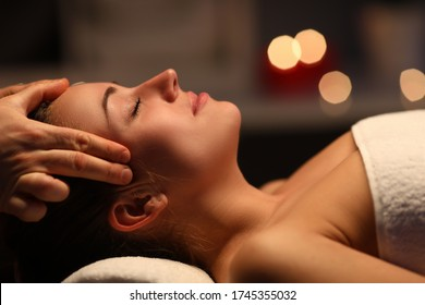 At home fingers massage head to beautiful girl. Girl lying at home under towel after massage. Pleasant sensations. Improve health in self-isolation. Massage using relaxation techniques