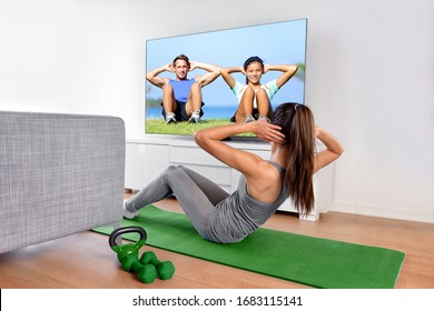 Home fitness concept. Woman doing strength training abs situps bodyweight floor exercises watching a dvd workout or web videos on a smart tv in the living room of a house or apartment.