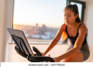 Home fitness fit woman exercising on smart stationary bike at home gym class watching screen online class biking exercise. Young girl training spinning the pedals pedaling. Focus on screen.