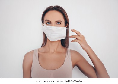 Home fitness. Young fit slim woman in sportswear protection face mask posing during self isolation quarantine. COVID-19 concept to promote stay safe home save lives. Free space for text mockup banner