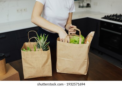 Home food delivery. Various vegetables and fruits in a paper bags that a young girl is sorting out at home on the kitchen table.