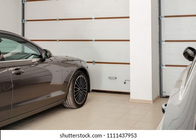 Home garage for two vehicles interior. Clean luxury cars parked at home. Automatic remote control doors. Transport roofed storage