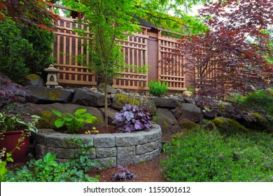 Home garden backyard landscaping with natural and stone stacked planter pots trellis lantern trees shrubs plants