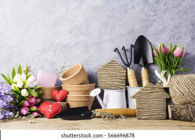 Home and garden concept of wood home with red heart and gardening tools and flowers on the old wood