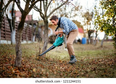 Home gardening details, young man cleaning up the garden using leaf blower
