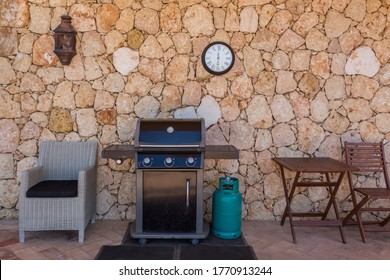 Home gas grill with cylinder, for family holidays and dinners. In the yard near the wall.