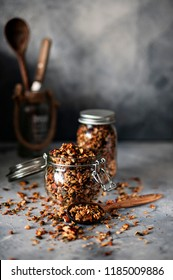 Home granola in a glass jar, on a gray concrete background. Close up.