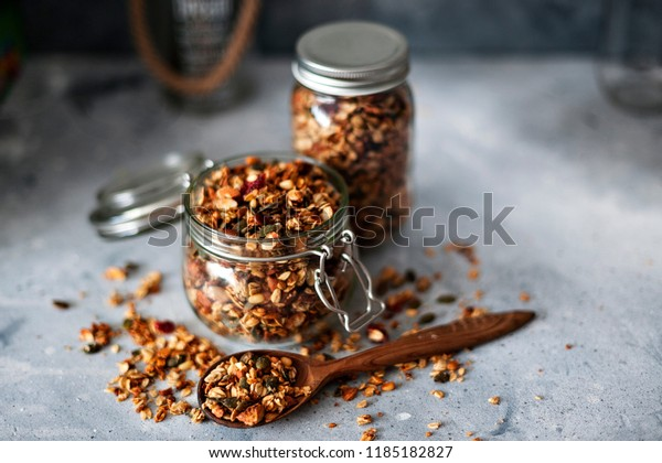 Home granola in a glass jar. Selective focus, concrete background.Healthy vegan snack