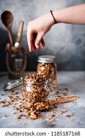 Home granola in two glass jars. Female hand nasypowa granola in a jar. Selective focus