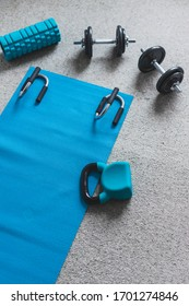 home gym concept, room with dumbbells kettlebell foam roller and push-up handles on yoga mat to workout from home