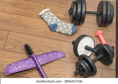 A home gym, dumbbells, and ab roller on the wooden floor