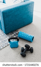 home gym and exercising indoor concept, set of fitness gear on living room carpet next to the couch in a living room shot at shallow depth of field