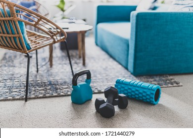 home gym and exercising indoor concept, set of fitness gear on living room carpet next to the couch in a living room shot at shallow depth of field - Shutterstock ID 1721440279