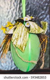 Home handmade happy easter ornaments, decoration, yellow, green egg hanged on wooden front brown door. Vertical composition.