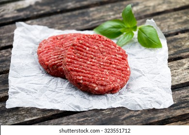 Home HandMade Minced Beef burgers decorated with Basil. on crumpled paper. wooden table.