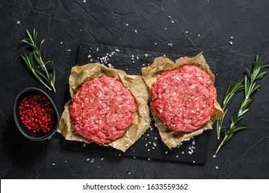 Home HandMade Raw Minced Beef steak burgers. Farm organic meat. Black background. Top view - Shutterstock ID 1633559362