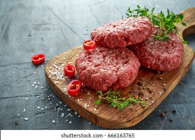 Home HandMade Raw Minced Beef steak burgers on wooden board.