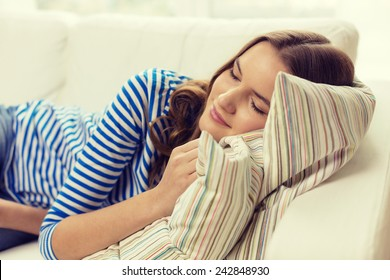 home and happiness concept - smiling teenage girl sleeping on sofa at home