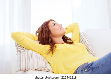 home and happiness concept - smiling young woman lying on sofa at home