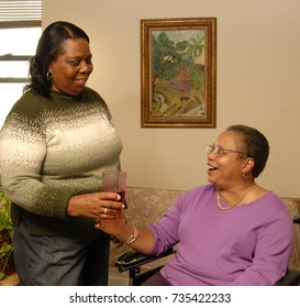 home health care aide, on our left, handing a glass of juice to her client, who's confined to a wheelchair in her apartment, Brooklyn, NY, March 8, 2016