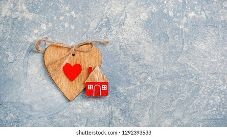 home and heart, symbol of love, family. design for Valentine's day greetings. Valentines day concept background. Wooden toy house on grey template. Concept of cozy, loving, protecting. Home sweet home